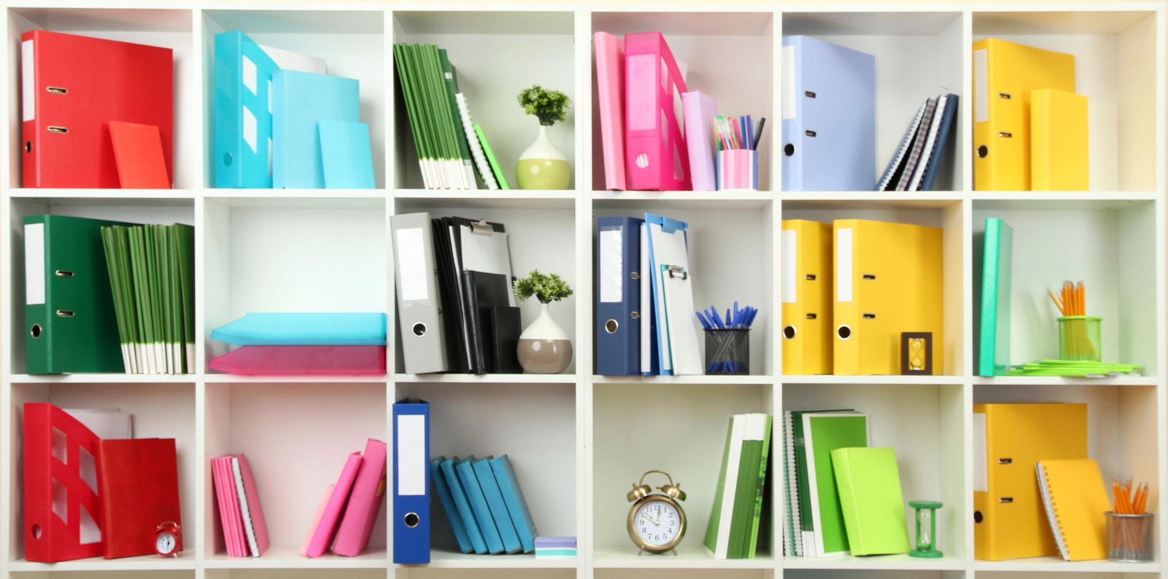 colorful bookkeeping binders on wall shelving unti